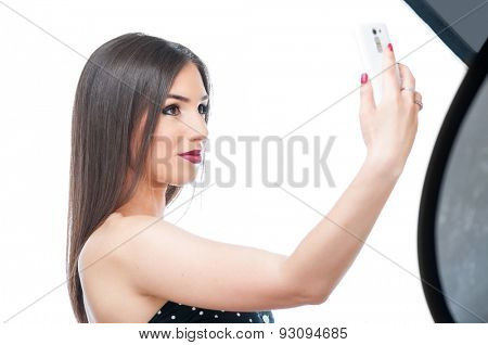 Young woman taking selfie in a studio for break time