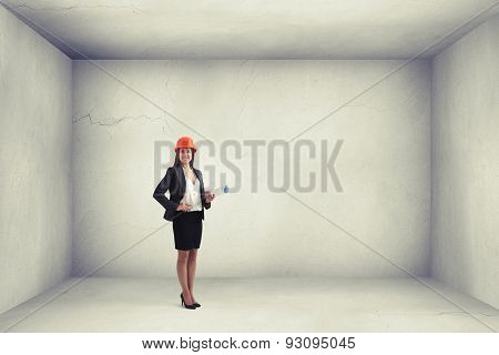 smiley woman architect in orange hardhat holding plan and looking at camera in empty concrete room with blank copyspace on the right