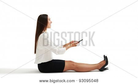 sideview photo of surprised woman in formal wear sitting on the floor and using her smartphone. isolated on white background