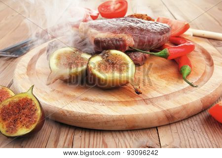 main entree : roasted beef lamb steak served with hot cayenne peppers green stuff sweet figs and cutlery on wood plate over wooden table