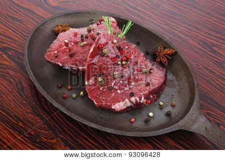 fresh raw beef fillet mignon on old retro style cast iron pan over retro wood table as background