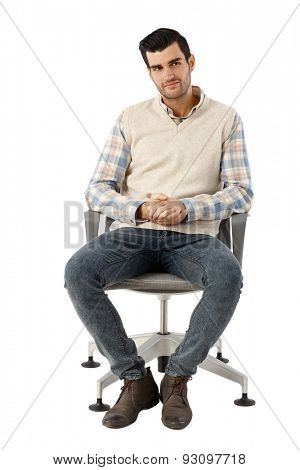Young businessman sitting in swivel chair over white background.