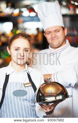 Waitress with tray cloche and cook chef at the indoor restaurant service