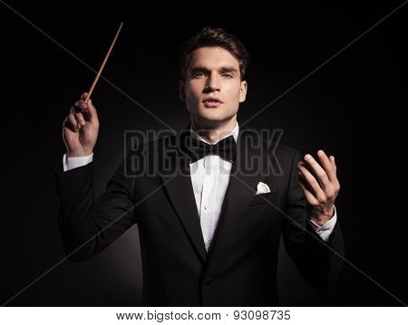 Handsome young man holding a stick in his hand, conducting an orchestra.