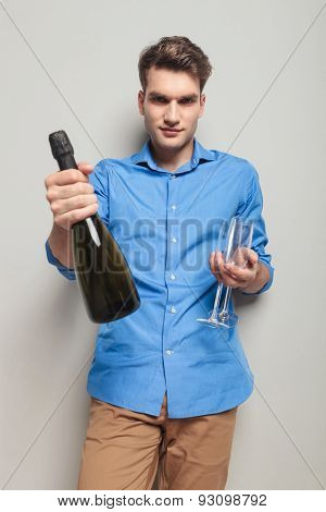 Handsome casual man giving you a bottle of champagne and holding two champagne glasses.