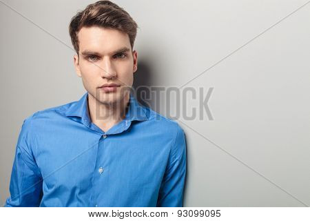 Portrait of a young casual man leaning on a grey wall while looking at the camera.