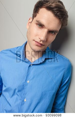 Close up picture of a young handsome man leaning his head on the wall, looking at the camera.