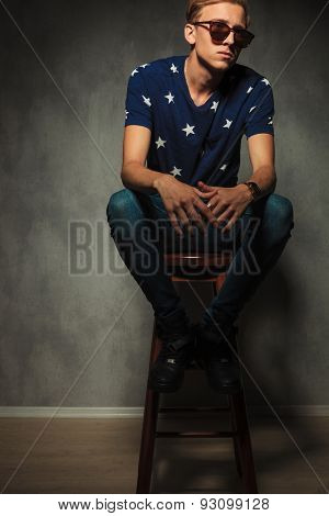 cut out image of a young fashion man sitting on a stool and looks away , studio shot