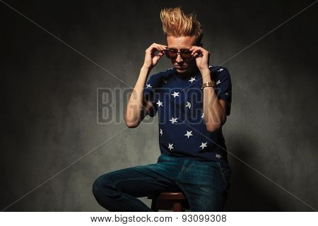 fashion man is taking off his sunglasses while sitting on a chair in studio