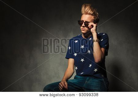 cool fashion holding his sunglasses while sitting on a chair in studio