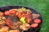 stock photo of baby back ribs  - Mixed Meat And Vegetables On The Hot BBQ Charcoal Grill - JPG