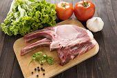 image of pork chop  - Fresh Raw Pork Chops and vegetables on wooden background - JPG