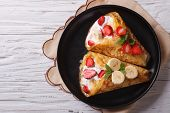 pic of crepes  - homemade crepes with fresh strawberries bananas and cream on a plate - JPG