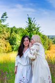 picture of national costume  - Two ukrainian girls in national costumes at the flower green meadow - JPG