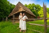 stock photo of national costume  - Two young woman in ukrainian national costumes near old wooden house  - JPG