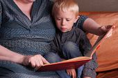stock photo of bible story  - Story time in the couch Woman reads the book to the little Child - JPG