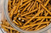 stock photo of pretzels  - A glass jar holds salted pretzel sticks