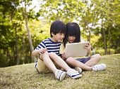 image of japan girl  - little asian girl and boy sitting on grass using digital tablet outdoors in a park - JPG