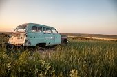 pic of discard  - An abandoned sedan sits discarded in a field - JPG