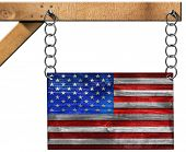stock photo of flag pole  - Wooden USA flag hanging from a metal chain on a wooden pole and isolated on white background - JPG