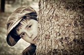 picture of newsboy  - Young boy with newsboy cap sneaking behind a tree and playing detective - JPG