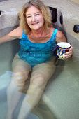 image of tub  - Mature female blond beauty relaxing in her hot tub.