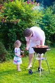 image of grilled sausage  - Father and child grilling meat. Family camping and enjoying BBQ. Dad and daughter at barbecue preparing steaks and sausages. Parents and kids eating grill meal outdoors. Garden fun for children.