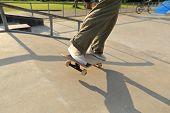 stock photo of skateboard  - skateboarder legs riding on skateboard skatepark ramp - JPG