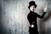 stock photo of pantomime  - Elegant expressive male mime artist posing with walking stick by a grunge wall - JPG