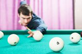 stock photo of snooker  - Young player man with cue playing billiard or snooker game - JPG