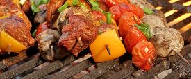 stock photo of charcoal  - Homemade BBQ Beef Shish Kabobs with Peppers and Mushrooms On The Hot Charcoal Cast Iron Grill Close - JPG