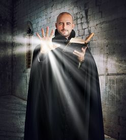foto of priest  - Priest with the Bible gives off light - JPG