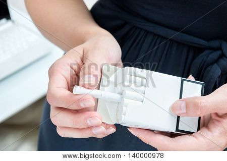Businesswoman break out a cigarette. Smoking in the workplace