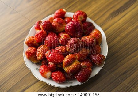 Bowl of strawberries top view on wooden table