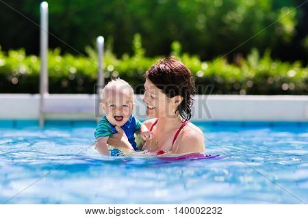 Happy young mother playing with her baby in outdoor swimming pool on hot summer day. Kids learn to swim during family vacation. Children wearing sun protection rash guard relaxing in tropical resort