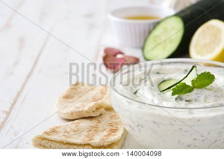 Tzatziki and ingredients on a white wooden table