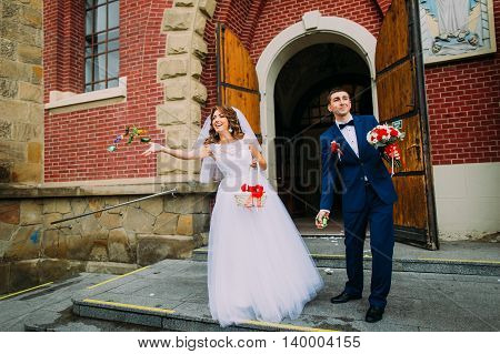 Happy bride and groom leaving the church after a wedding ceremony.