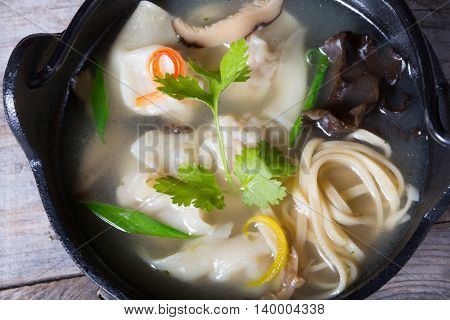 Asian dumplings soup served in metal bowl