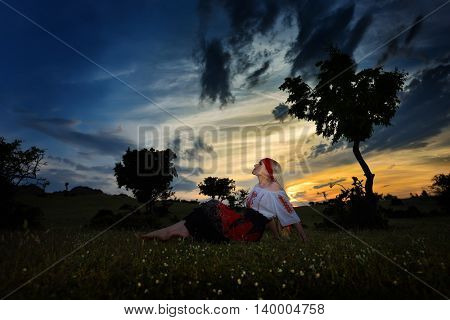 beautiful woman on field at sunset, summer evening
