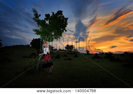 beautiful woman on field at sunset, summer evening