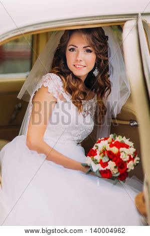 Happy newlywed bride is sitting on a backseat of vintage car.