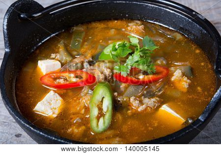 Asian soup with tofu served in metal bowl