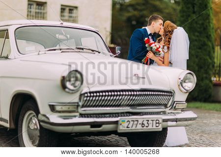 Happy newlywed couple kissing beside of vintage car.