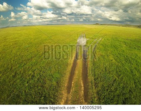 Ground road and cloudy sky in the steppes of Kazakhstan. Aerial photography.