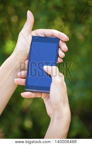 Side view of a woman's hand holding a modern slick smartphone while dialing with her thumb against summer green background