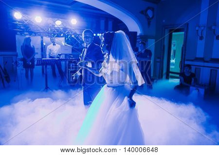 Wedding dance of newlywed couple. The hall is covered with white fume and filled by blue lights.