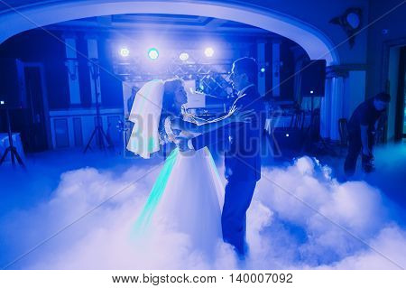 First dance of newlywed couple. The hall is covered with white fume and filled by blue lights.