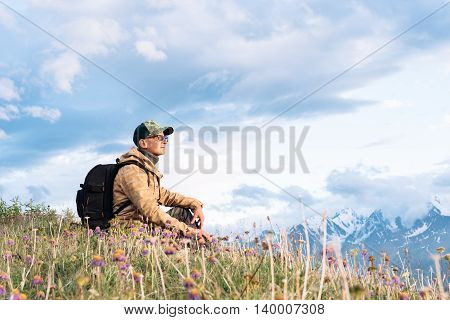 traveler with a backpack and wearing a cap and glasses sitting on top of a mountain and looks into the distance dreaming look