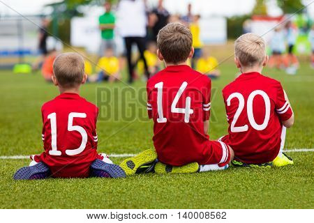 Young boys in soccer team sitting together on the sports field. Kids as a reserve soccer football players. Football soccer match tournament for children teams.