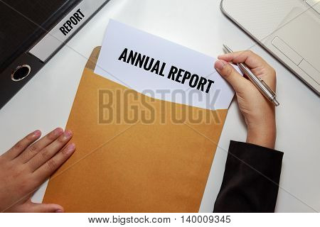Businesswoman opening Annual report document in letter envelope - business concept